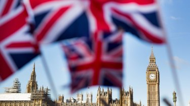 A display of Union Jack flags fly in front of the Houses of Parliament, in London.