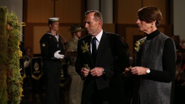 Prime Minister Tony Abbott and his wife Margie place a floral tribute on the wreath at the National Memorial Service for MH17 at Parliament House on Friday.