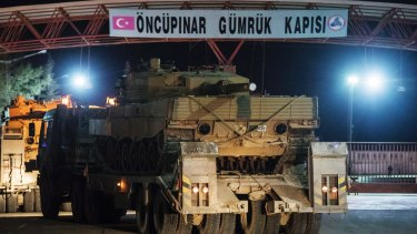 Turkish military trucks carrying tanks and other armoured vehicles cross through a border gate into a Turkish-controlled region of the Oncupinar border crossing with Syria. The deployment occurred hours after dozens of Turkish jets bombed Syrian Kurdish militia targets in the enclave of Afrin.