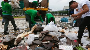 Workers cut fake handbags in a symbolic destruction of counterfeit goods in the Philippines in July this year.
