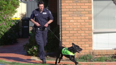 A police officer runs around the Seabrook house raided on Tuesday morning.