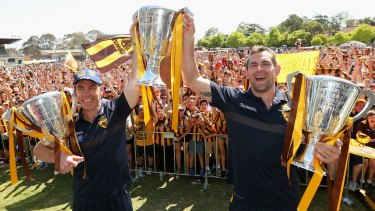 Alastair Clarkson and Luke Hodge show off Hawhtorn's trio of premiership trophies.