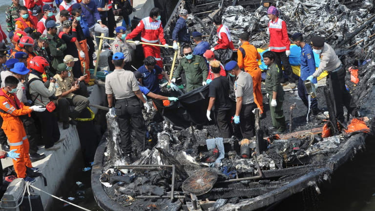 Rescuers search for victims from the wreckage of a ferry that caught fire off the coast of Jakarta.