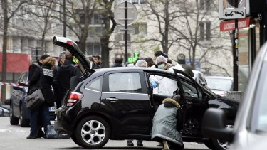 French police officers and forensic experts examine the car used by armed gunmen who stormed the Paris offices of satirical magazine <i>Charlie Hebdo</i>