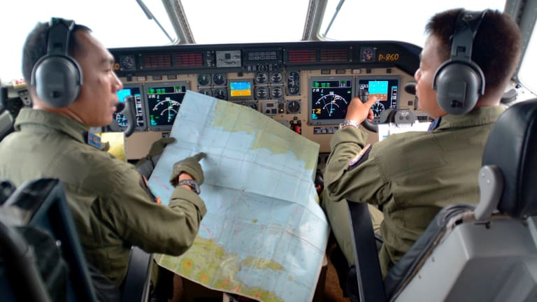 Pilot of navy airplane CN235 M. Naim holds a map to co-pilot Rahmad while flying over the Java sea during joint search operations for QZ8501.