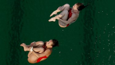 """""""It's so green"""": United States' Amy Cozad, top, and Jessica Parratto before diving into the green pool."""