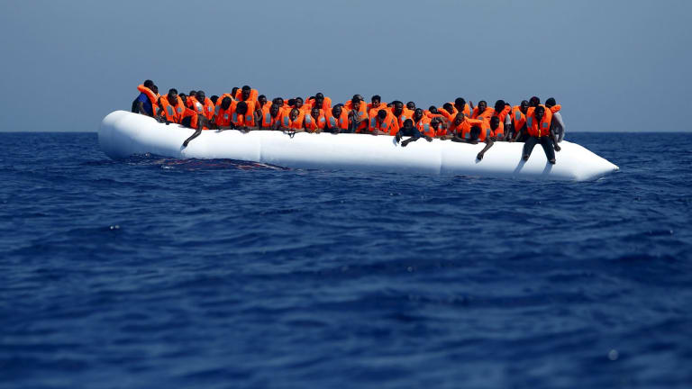 Migrants on a rubber dinghy wait to be rescued by a Migrant Offshore Aid Station ship off the coast of Libya in August.