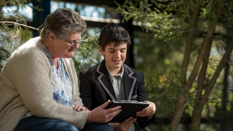 Ben, a student at Mount Eliza Secondary College teaching Jann Bell how to listen to the radio via her iPad.