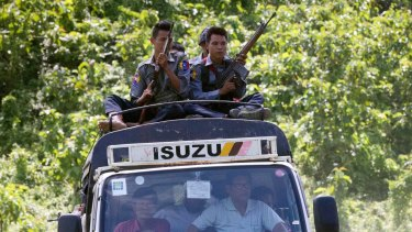 Myanmar police travel on the roof of a truck carrying local UN staff as they flee the violence on August 28.