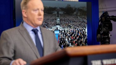 An image of the inauguration of President Donald Trump is displayed behind White House press secretary Sean Spicer as he speaks at the White House.
