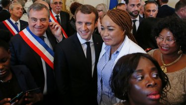 French President Emmanuel Macron with people who became French citizens during a citizenship ceremony in Orleans on Thursday.