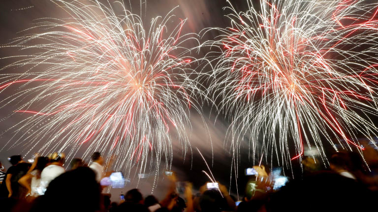Filipino revelers watch as fireworks light up the sky to welcome the New Year at the seaside Mall of Asia in suburban Pasay city, south of Manila.