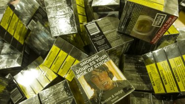 A pile of cigarette packets with plain packaging.