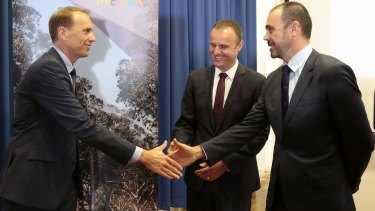 From left, ACT Deputy Chief Minister Simon Corbell, Chief Minister Andrew Barr and Canberra Metro Consortium chairman Mark Lynch shake hands as the winning tender is announced on February 1.