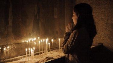 A Damascus woman prays in St Sarkis.