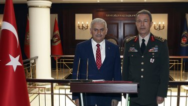 """Turkey's Prime Minister Binali Yildirim, left, says Turkey is recalling its ambassador to Germany after what he calls a """"historic error"""" by the German parliament."""