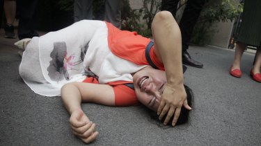 Fan Lili, wife of imprisoned activist Gou Hongguo, on the ground after an interaction with a police officer outside the Tianjin court.