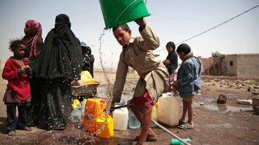 A boy rinses a bucket as he collects water from a well on the outskirts of Sanaa that is reportedly contaminated with cholera bacteria.