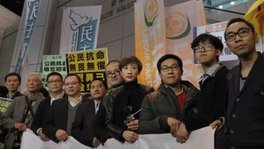 From right, former student leaders Eason Chung, Tommy Cheung, activist Raphael Wong, lawmakers, Tanya Chan, Shiu Ka-chun, former legislator Lee Wing-tat, founders of the Occupy Central civil disobedience movement, Benny Tai, Chan Kin-man and Chu Yiu-ming pose for a picture before walking toward a police station in Hong Kong on Monday.