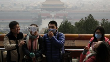Visitors, some wearing masks to protect themselves from pollution, in Jingshan Park on a polluted day in Beijing, last December.
