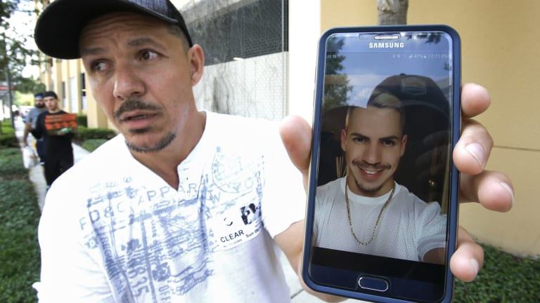 Angel Mendez, outside the Orlando Regional Medical Centre, holds up a phone photo trying to get information about his brother Jean C. Mendez who was at the Pulse Nightclub.