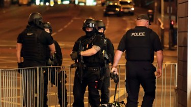 Armed police work after an explosion at the Manchester Arena in Manchester, England.