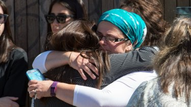 Mourners comfort each other at the memorial service for Thalia Hakin.