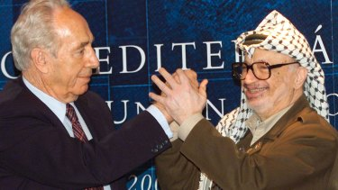 Then: Palestinian leader Yasser Arafat, right, clasps hands with Israeli Foreign Minister Shimon Peres in 2001.