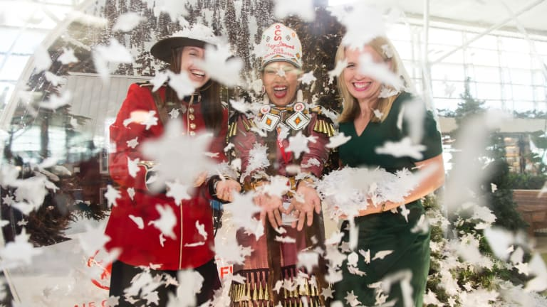 A Canadian Mountie, the First Nation Calgary Princess and Tourism Minister Kate Jones inside the giant snow dome at Brisbane International Airport.