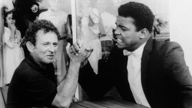 Novelist Norman Mailer is shown arm wrestling with heavyweight champion Muhammad Ali on the terrace of their San Juan hotel, in  1965.
