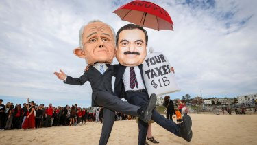 Two protestors wear masks depicting Malcolm Turnbull and Adani founder Gautam Adani. Photo: Katherine Griffiths