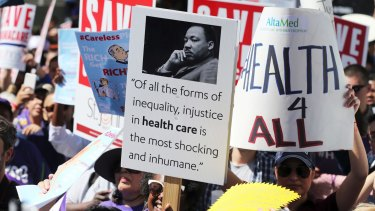Hundreds of people march through downtown Los Angeles protesting Trump's plan to dismantle the Affordable Care Act.