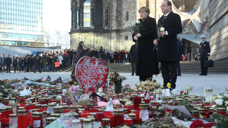 French President Francois Hollande and German Chancellor Angela Merkel prepare to lay flowers at a memorial to the victims of the December Berlin terror attack at Breitscheidplaz in Berlin, Germany.