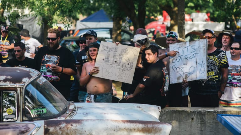 Men hold up signs along Tuff Street during Summernats.