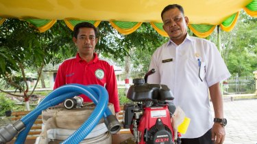 The Fire-Free Village program's local liaison (left) and Pelalawan's deputy head of village, Edi Hanafi, with the motorised water pump the village bought with the program's half-reward.