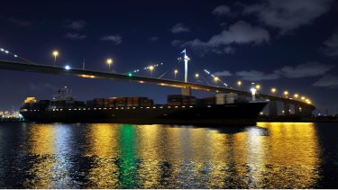 A container ship sails down the Yarra River under the West Gate Bridge after leaving the Port of Melbourne.
