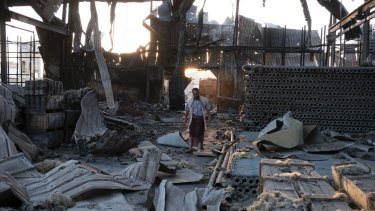 A man walks through the remains of a factory that was bombed twice in September outside of Yemen's capital Sanaa.