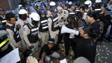 Police block human rights activists during  their candlelight vigil in Phnom Penh on Monday.