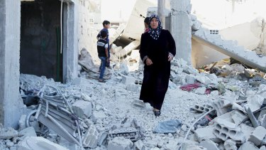 Residents inspect damage from what activists said were barrel bombs dropped by Syrian regime forces in the town of al-Hara, in Syria's southern Daraa province.