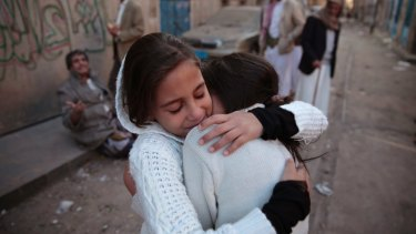 Girls react as they stand near their house which was damaged by a Saudi-led airstrike last Saturday.