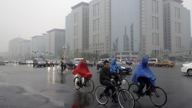 Residents ride their bicycles  along Chang'an Avenue on a hazy day in central Beijing in March.