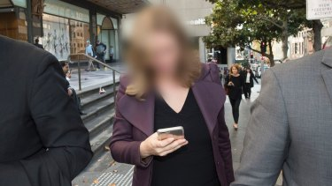 The woman, who cannot be identified, leaves the Downing Centre court complex on Thursday.