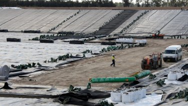 Contractors lay the lining at a Santos waste water pond in the Pilliga.