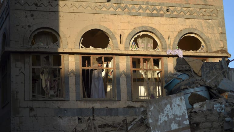 A boy looks from the window of his damaged house at the site of a Saudi-led airstrike near Yemen's Defence Ministry complex in Sanaa last Saturday.