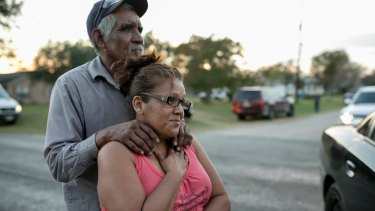 Enrique and Gabby Garcia watch investigators at the scene of a mass shooting at the First Baptist Church in Sutherland Springs.
