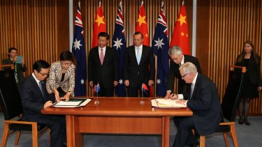 Chinese President Xi Jinping (rear) and then-prime minister Tony Abbott witness the signing of the declaration of intent on the free trade agreement late last year.