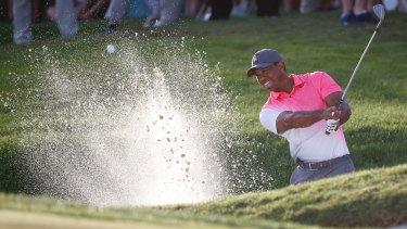 Tiger Woods hits out of a bunker on the 18th.