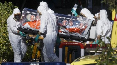 Infected: Health workers transfer Miguel Pajares, who has since died, in Madrid.
