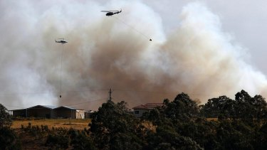 A water bombing helicopter fights the bushfire at Richmond Vale near Cessnock.