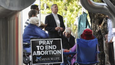 Catholic Archbishop of Canberra and Goulburn Christopher Prowse, centre, attends a prayer vigil outside the Moore Street abortion clinic in March.